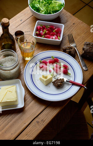 plate with radish and butter on a table - Stock Photo