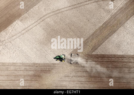 An aerial view of farm machinery plowing under a wheat field in preparation for the next years crop. - Stock Photo