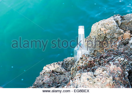 Empty bottle of rum left in a rock where fishermen spend hours trying to catch something while camping in Cabagan - Stock Photo