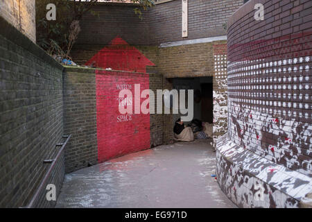 Homeless woman sat under cover at an underpass in the City of London, UK. Sitting huddled and wrapped up from the - Stockfoto