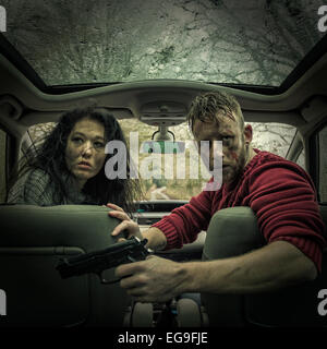 Man and woman in car with handgun - Stockfoto