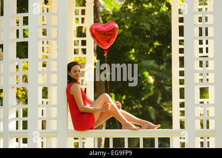 Woman with red heart shape balloon sitting on park bench - Stockfoto