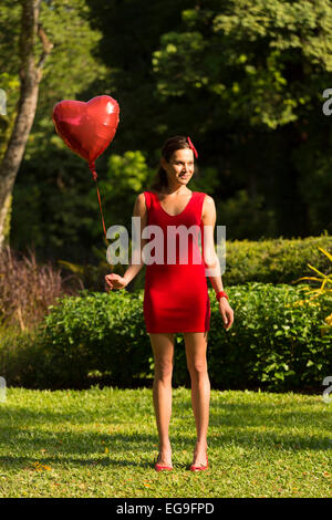 Woman with red heart shape balloon standing in park - Stockfoto