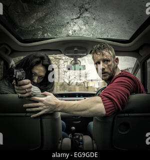 Couple in car with gun - Stockfoto