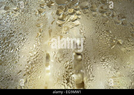 Abstract background. Golden drops of water on the glass material. - Stock Photo