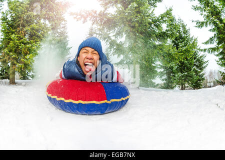 Crazy boy on snow tube in winter fir forest - Stock Photo