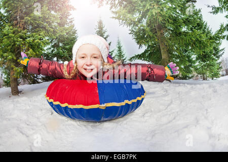 Smiling girl on snow tube in winter during day - Stock Photo