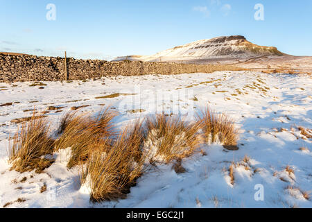 Golden hour over a snow covered Pen-y-ghent in the Yorkshire Dales National Park. - Stock Photo
