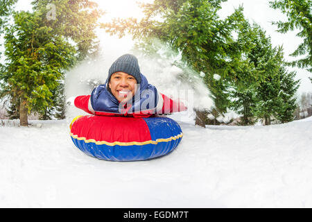 East Asian boy on snow tube in winter alone - Stock Photo