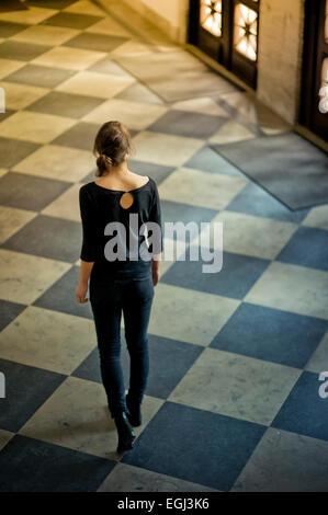 Young woman walking on tiled floor, - Stockfoto