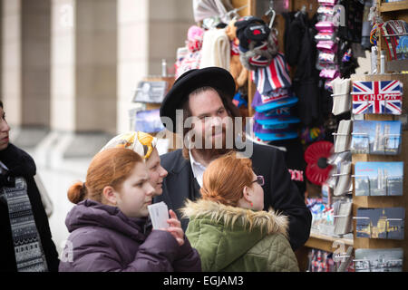 Jewish tourists looking at postcards from London at a kiosk in Westminster, London, UK - Stock Photo