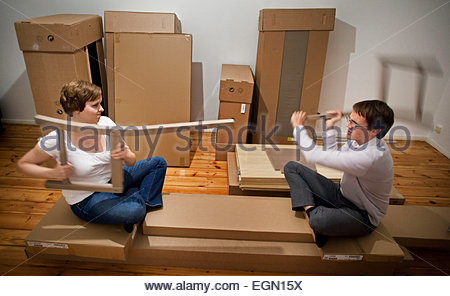 Young couple arguing during the building up of the furniture, Berlin, Germany - Stock Photo