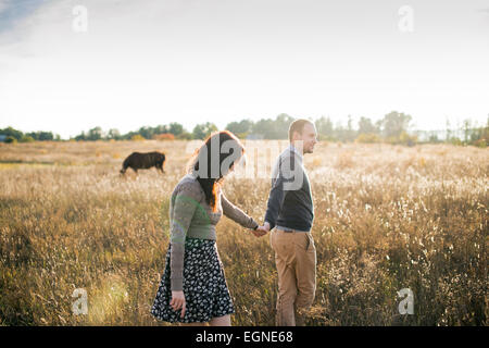 Image of a young couple that walks holding hands at autumn sunset. Horses on the background. - Stock Photo