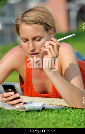 Woman lying in the grass looking at her iphone - Stock Photo