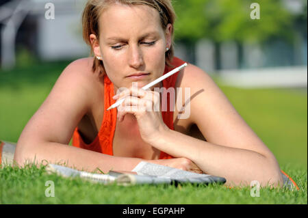 Woman lying in the grass reading a newspaper - Stock Photo