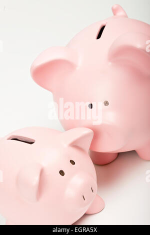 Elevated view of two pink piggy banks, of different sizes, against a white background. - Stockfoto