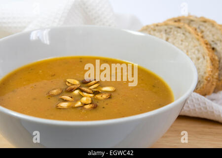 Spicy homemade roasted butternut squash soup with roasted butternut squash seeds sprinkled on top, in a white bowl - Stock Photo