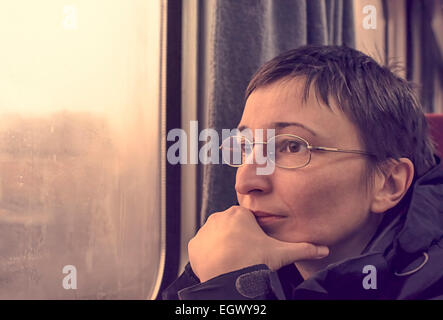 Portrait of worried woman in train. Thinking and wondering concepts. - Stock Photo