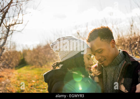 Two people, a couple walking in an orchard in winter. - Stock Photo