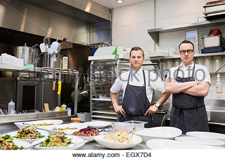 Portrait of confident chefs in commercial kitchen - Stock Photo