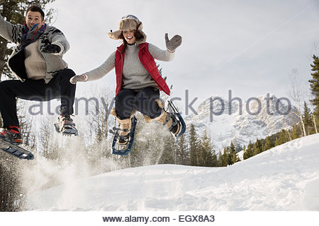 Couple jumping in snowshoes below snowy mountain - Stockfoto