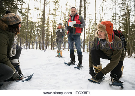 Friends putting on snowshoes in snowy woods - Stock Photo