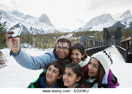 Family taking selfie below snowy mountains - Stockfoto