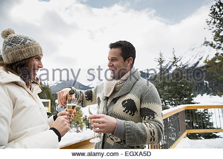 Couple drinking champagne on snowy deck below mountains - Stock Photo
