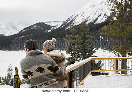 Couple drinking champagne on deck below snowy mountains - Stock Photo