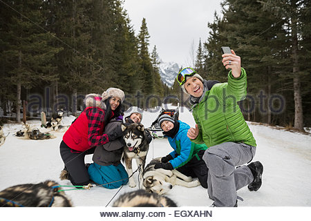 Family taking selfie with dogsled dogs in snow - Stockfoto