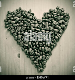 a pile of roasted coffee beans forming a heart, on a wooden table , in black and white - Stock Photo