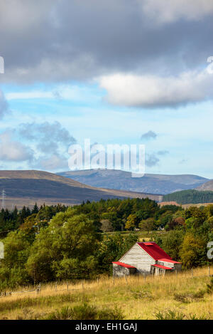 Red-roofed wooden hut in a rural area of the Cairngorms, Scotland under a partly cloudy autumn sky - Stock Photo