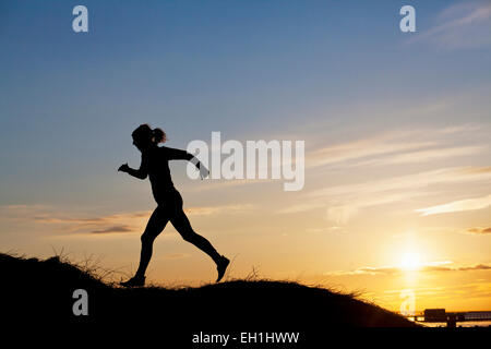 Silhouette female runner on hill during sunset - Stock Photo