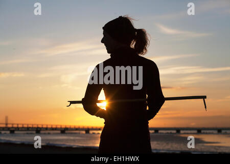 Silhouette female jogger with stick at beach during sunset - Stock Photo