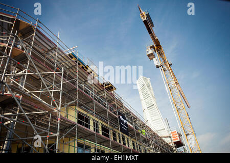 Low angle view of crane in front of building under construction - Stock Photo