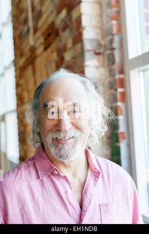 Portrait of happy senior man in gym - Stock Photo