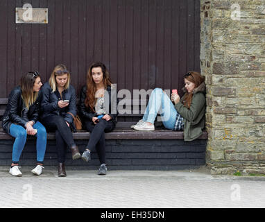 Teenager females spend half term winter school holiday playing on smart phones whilst away from parents at seaside - Stock Photo