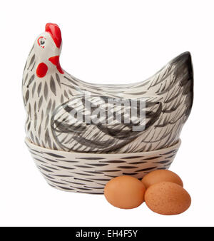 Ceramic egg container in the shape of a hen, lined with straw and containing brown eggs. - Stock Photo