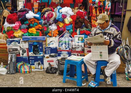 Ecuador, Cotopaxi, Zumbahua, day of the village of Zumbahua market, trader reading the newspaper in front of his - Stock Photo