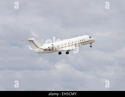Business jet taking off to the cloudy sky - Stock Photo