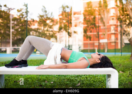 Fitness woman doing exercises in the city park - Stock Photo