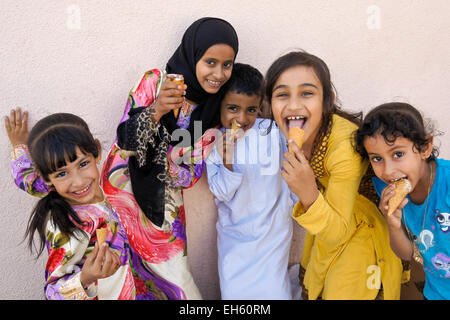 Children eating ice cream cones and being silly, Nizwa, Oman - Stock Photo