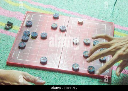 Two men playing, vietnamese chess board game, XiangQi - Stock Photo