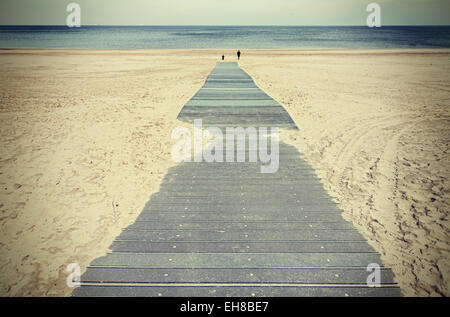 Retro toned photo of a boardwalk on beach. - Stock Photo