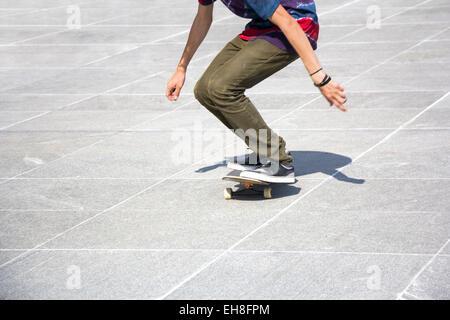 Skateboarder riding skateboard on concrete slabs - Stock Photo