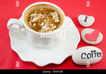 White cup of coffee with decorated foam and rocks saying 'I love coffee' - Stock Photo