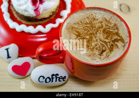 Red cup of coffee with decorated foam and pebbles saying 'I love coffee' - Stock Photo