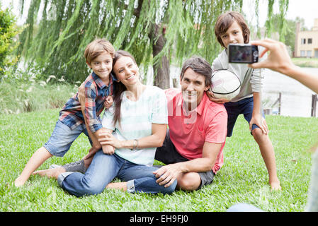 Using digital camera to photograph family with two children, personal perspective - Stock Photo