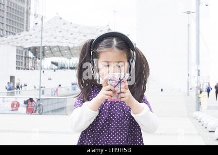 Girl looking at smartphone and listening to headphones outdoors - Stock Photo