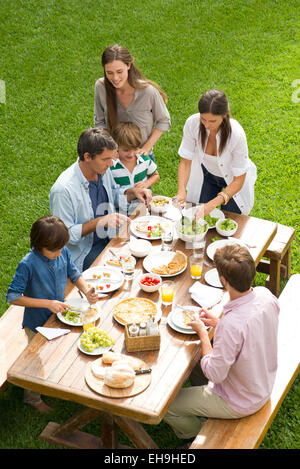 Family and friends enjoy healthy meal outdoors - Stock Photo